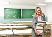 Teacher. Portrait of smiling teacher holding books Stock Photo
