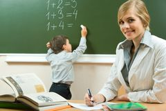 Teacher. Portrait of pretty teacher sitting at the table on the background of schoolboy royalty free stock photo