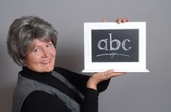 Teacher with ABC. Kind older teacher with a mini blackboard and letters on it Stock Image