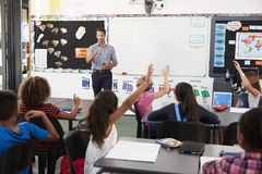 Teacher addressing pupils in an elementary school lesson stock photography