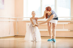 Teacher adjusting position of young ballerinas at barre. Ballet teacher adjusting position of young ballerinas at barre Royalty Free Stock Photos