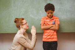 Teacher apologizing boy in classroom. Female teacher apologizing boy in the classroom Royalty Free Stock Photography