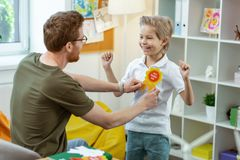 Beaming active kid in white t-shirt having bright rewarding sign. Teacher applying sign. Beaming active kid in white t-shirt having bright rewarding sign for royalty free stock photos