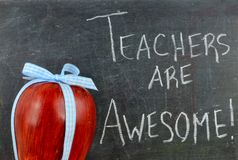 Teacher appreciation image of a red apple tied up with a cute blue ribbon. In front of a worn blackboard with a message written in white chalk stock image