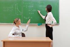 Teacher asks student at blackboard Stock Photos