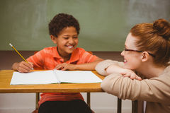 Teacher assisting boy with homework in classroom Royalty Free Stock Photos