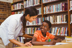 Teacher assisting boy with homework in library Royalty Free Stock Photos
