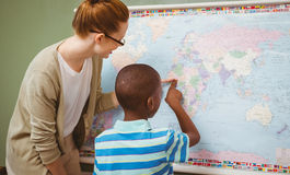 Teacher assisting boy to read map in classroom Stock Photography