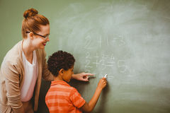 Teacher assisting boy to write on blackboard in classroom Stock Image