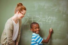 Teacher assisting boy to write on blackboard in classroom Stock Photo