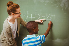 Teacher assisting boy to write on blackboard in classroom Stock Images