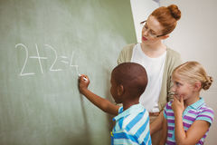 Teacher assisting boy to write on blackboard in classroom Stock Photography