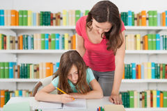Teacher Assisting Girl At School Library Stock Photos