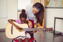 Teacher assisting a girl to play a guitar in classroom Royalty Free Stock Photography