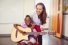 Teacher assisting a girl to play a guitar in classroom Stock Photography