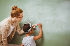 Teacher assisting girl to write on blackboard in classroom Royalty Free Stock Photo