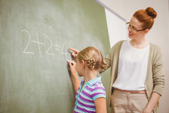 Teacher assisting girl to write on blackboard in classroom Royalty Free Stock Images