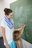 Teacher assisting girl writing on chalkboard in classroom Stock Photography