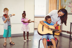 Teacher assisting a kids to play a musical instrument in classroom Stock Photography