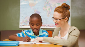 Teacher assisting little boy with homework in classroom Royalty Free Stock Photo