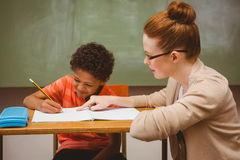 Teacher assisting little boy with homework in classroom Royalty Free Stock Image