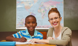 Teacher assisting little boy with homework in classroom. Portrait of teacher assisting little boy with homework in the classroom Stock Photos
