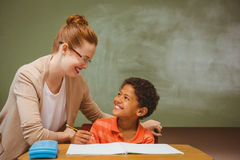 Teacher assisting little boy with homework in classroom Stock Photos