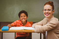 Teacher assisting little boy with homework in classroom Stock Images