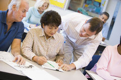 Teacher assisting mature student in class Stock Photos