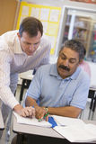 Teacher assisting mature student in class Royalty Free Stock Image