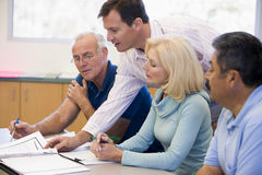 Teacher assisting mature students in class Stock Photo
