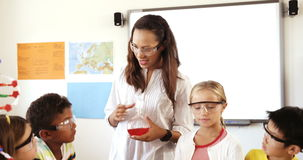 Teacher assisting school kids in doing experiment in classroom stock footage