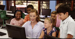 Teacher assisting school kids on personal computer in classroom stock footage