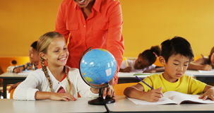 Teacher assisting school kids in reading globe in classroom stock video footage