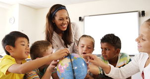Teacher assisting school kids in reading globe in classroom