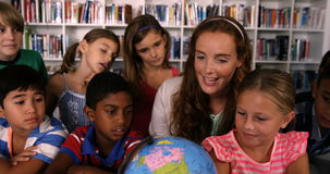 Teacher assisting school kids in reading globe in library stock footage
