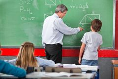 Teacher Assisting Schoolboy While Solving. Mature male teacher assisting little schoolboy while solving mathematics on board in classroom Stock Image