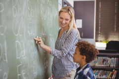 Teacher assisting schoolboy in writing alphabet on chalkboard Stock Photography