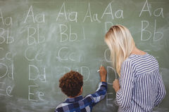 Teacher assisting schoolboy in writing alphabet on chalkboard Stock Image