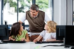 Teacher Assisting Schoolchildren In Using Desktop Stock Photos