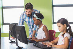 Teacher assisting schoolgirls in learning computer Royalty Free Stock Photo