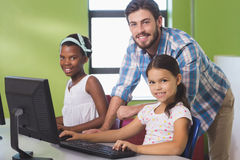 Teacher assisting schoolgirls in learning computer Royalty Free Stock Photography