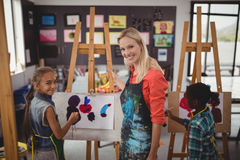 Teacher assisting schoolkid in drawing class Royalty Free Stock Photos
