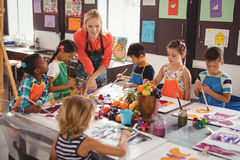 Teacher assisting schoolkids in drawing class Stock Photo