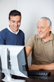 Teacher Assisting Senior Man In Computer Class Stock Photos