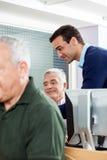 Teacher Assisting Senior Man In Computer Class Stock Photo