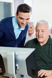 Teacher Assisting Senior Man In Computer Class. Young male teacher assisting senior men in computer class Royalty Free Stock Photo