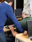 Teacher Assisting Senior Man At Computer Desk Stock Images