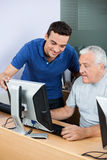 Teacher Assisting Senior Man In Using Computer At Classroom Stock Photography