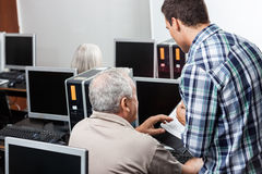 Teacher Assisting Senior Man In Using Computer At Classroom Stock Photos